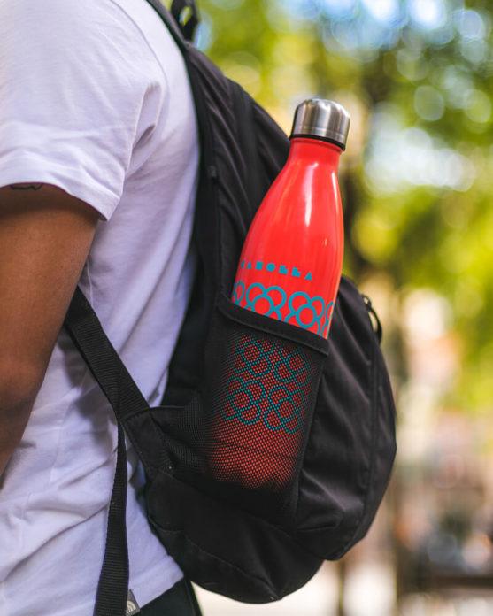 Imagen de producto botella Panot BCN roja en una mochila